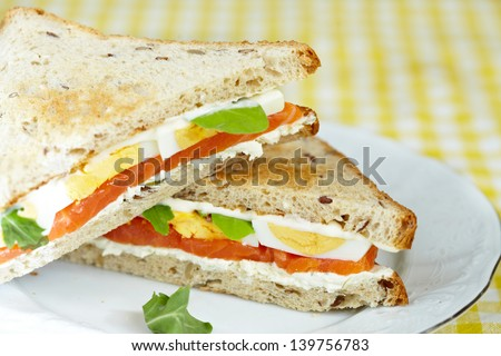 Sandwich with smoked salmon, cream cheese,eggs and arugula