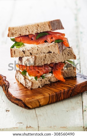 Sandwich with smoked salmon red fish on blue wooden background - stock photo