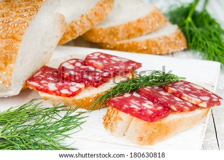 Sandwich with smoked sausage on the chopping board