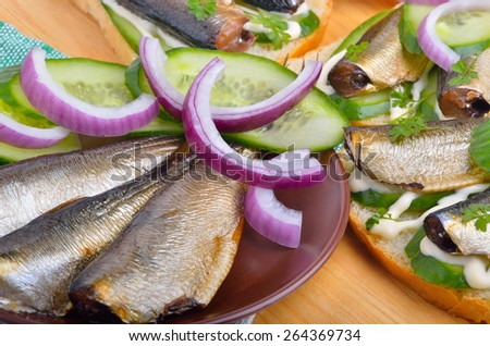 Sandwich with sprats and green cucumber on a plate - stock photo