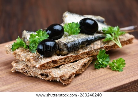 Sandwich with sprats and olives on crispbread, close up view - stock photo