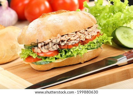 Sandwich with tuna and tomato on wood background