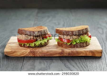 sandwich with tuna and vegetables on rye bread on wood background - stock photo