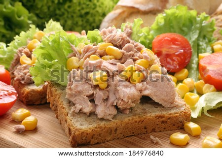 Sandwich with tuna, corn and tomato on wood - stock photo