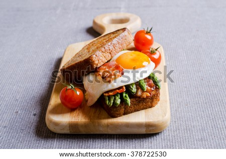 Sandwich with vegetables, egg and bacon. Selective focus. - stock photo