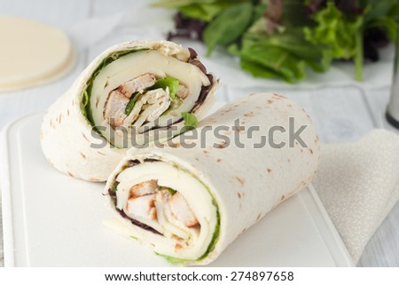 sandwich wrap or tortilla with leftover meat, cheese and lettuce on white chopping board - stock photo