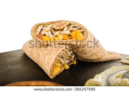 Sandwich Wrap or Tortilla with Leftover Meat, Cheese Pork and Corn on Black Chopping Board Over White. Tasty Fast Food, Mexican Burrito with Chicken or Beef Meat and Vegetables. Delicious Healthy Meal - stock photo