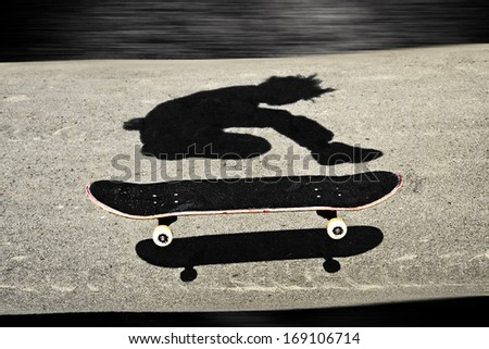 sandwiched skateboard in between shadows of a boy skateboarding - stock photo