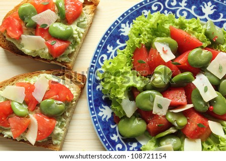 Sandwiches and broad beans salad with tomato and goat cheese - stock photo