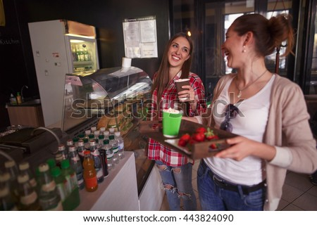 Sandwiches and snacks concepts. Toned image of happy ladies choosing dishes for eating. Cheerful women having break in cafe or restaurant.