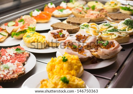 Sandwiches from catering service on plate at a buffet with cold meat, eggs and cheese