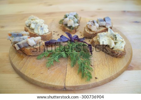 Sandwiches of rye bread and herring. Pieces of fish are herring on bread. Sandwiches with bread and fish on a wooden boards background. Traditional appetizer Scandinavian. Fish on the wooden board. - stock photo