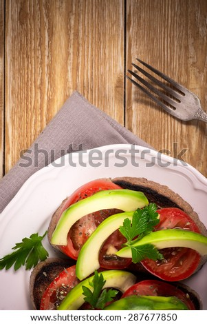 Sandwiches of rye bread with avocado and tomatoes on wooden background
