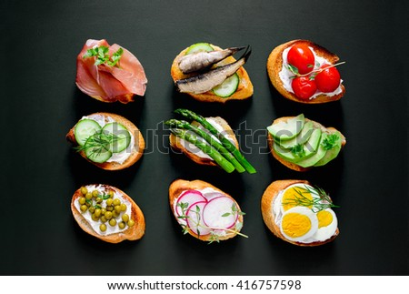 Sandwiches on a dark background, or assorted canapes, top view - stock photo