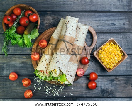 Sandwiches twisted roll Tortilla burritos three pieces on a wooden cutting board on a gray background, lettuce, cucumbers malosollnye, cherry tomatoes, corn, onion rings, meat, top view - stock photo