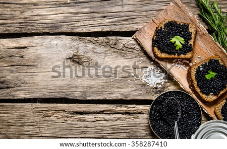 Sandwiches with black caviar, a jar of caviar and a spoon. On a wooden table. Free space for text . Top view - stock photo