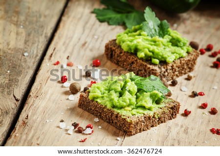Sandwiches with black rye bread and avocado mousse with spices, selective focus - stock photo