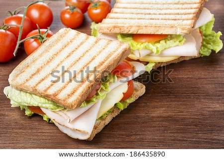 Sandwiches with chicken breast, salad, cheese and tomatoes on wooden table