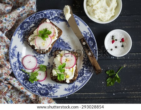 sandwiches with cream cheese and radish on a vintage plate on a dark wooden background - stock photo