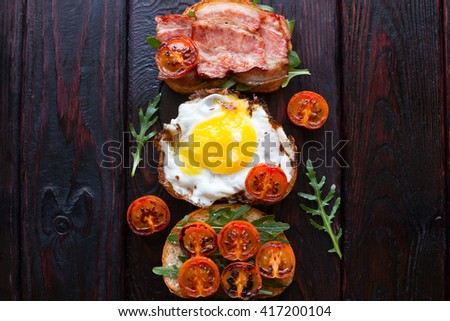 sandwiches with egg and bacon tomatoes and arugula - stock photo