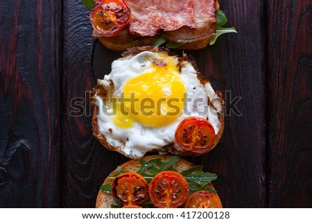 sandwiches with egg bacon and tomato on a black background - stock photo