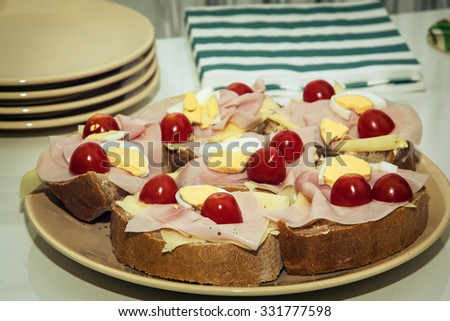Sandwiches with egg, cheese, ham and cherry tomatoes. Food and drink theme. Toned photo.