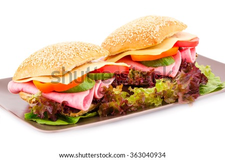 Sandwiches with fresh vegetables, ham and cheese on plate. - stock photo