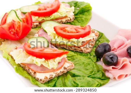 Sandwiches with fresh vegetables, olives, bacon and ham on plate. - stock photo