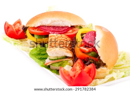 Sandwiches with fresh vegetables, salami and cheese on plate. - stock photo