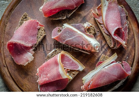 Sandwiches with  italian ham on the wooden board - stock photo