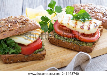 Sandwiches with pesto, tomatoes and grilled haloumi - stock photo
