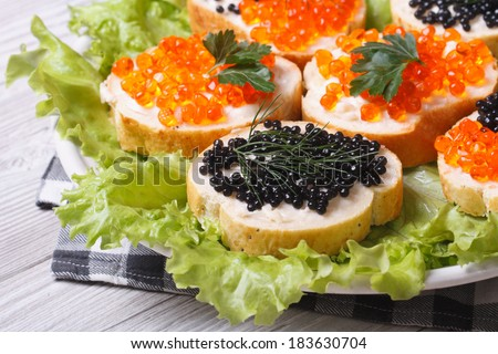Sandwiches with red and black fish caviar with lettuce closeup horizontal  - stock photo