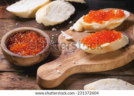 Sandwiches with red caviar served on olive wood cutting board over old wooden table. See series - stock photo