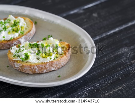 sandwiches with ricotta cheese, olive oil, pistachios and herbs is a delicious and healthy Breakfast or snack, on an oval plate on a wooden surface - stock photo
