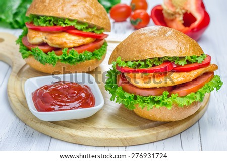 Sandwiches with roast chicken fillet, tomato and paprika on wooden board - stock photo