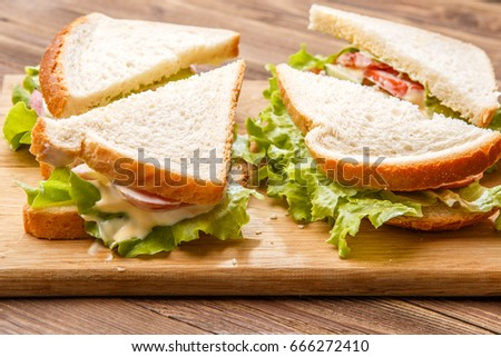 Sandwiches with salad and sausage on wooden board