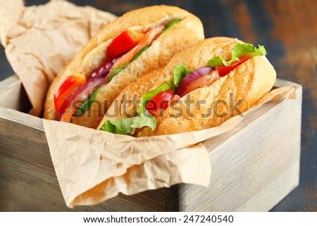 Sandwiches with salmon in wooden box on dark wooden background