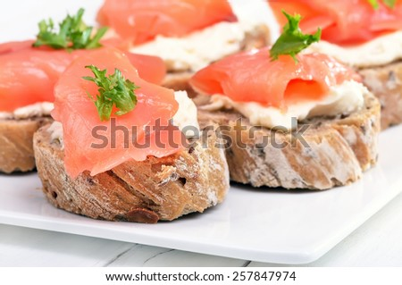 Sandwiches with salmon on white plate, close up view - stock photo