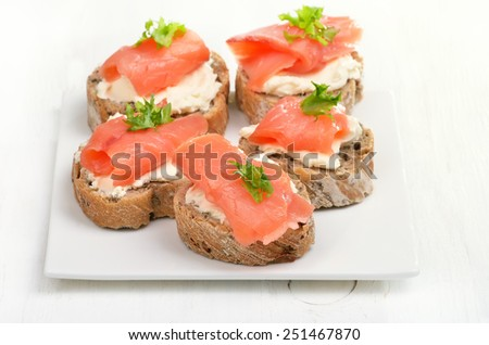 Sandwiches with salmon on white plate on wooden table - stock photo