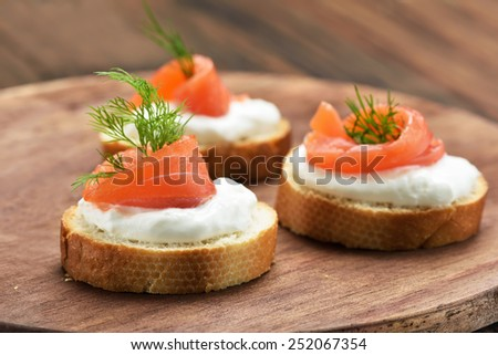 Sandwiches with salmon on wooden cutting board