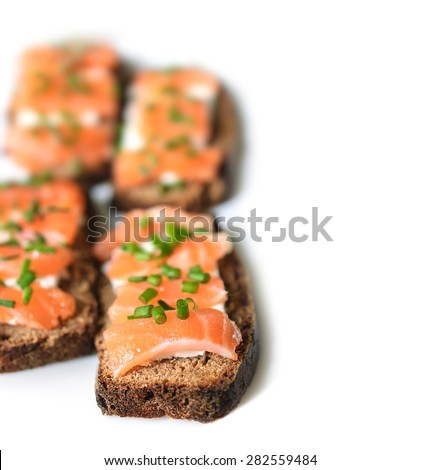 Sandwiches with salted salmon, rye bread, cream cheese and finely chopped green onions on a white background. Selective Focus, Focus on the front of the sandwiches - stock photo