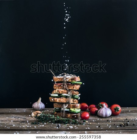 Sandwiches with smoked meat, cucumber and herbs tied with a rope, placed one over another. Salt is being strewed on them from above on them  - stock photo