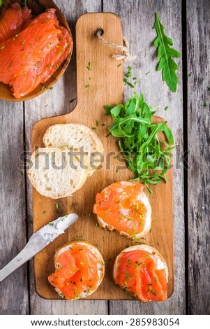 sandwiches with smoked salmon with cream cheese, arugula on wooden cutting board - stock photo
