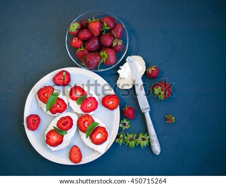 Sandwiches with soft cheese, ripe berries and leaves of mint. Food composition on a blue background. Top view. Selective focus. - stock photo