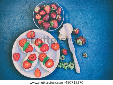 Sandwiches with soft cheese,ripe berries and leaves of mint. Food composition on a blue background. Top view. Selective focus. - stock photo