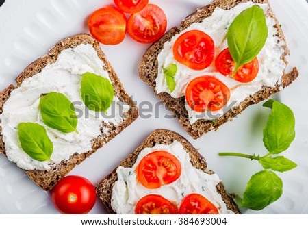 Sandwiches with soft cream cheese, cherry tomatoes and fresh basil on white plate - stock photo