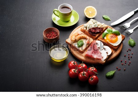 Sandwiches with various useful and tasty fillings such as ham, egg, cheese, dried tomatoes and fresh vegetables. The concept of useful and tasty breakfast. Place for writing text or recipe. - stock photo