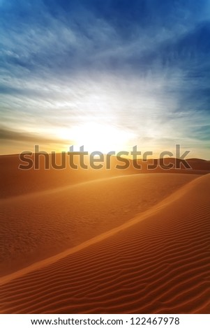 Sandy barkhans in the evening. The sun with beams in the desert.