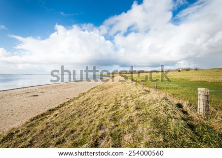 Sandy beach and a dike with some grazing sheep along a Dutch estuary on a sunny and cloudy day in the winter season. - stock photo