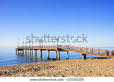 Sandy beach and a wooden pier on Costa del Sol between resort town of Marbella and Puerto Banus in Spain, Malaga province. - stock photo
